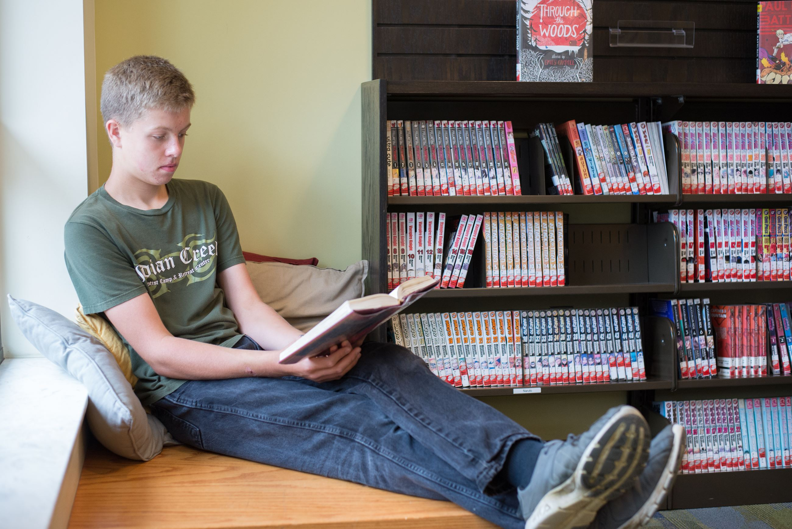 Image of a Teen boy sitting on a bench reading a book in the Teen Zone